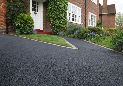 New bitumen driveway outside a beautiful brick house in London. Plenty of space for text.